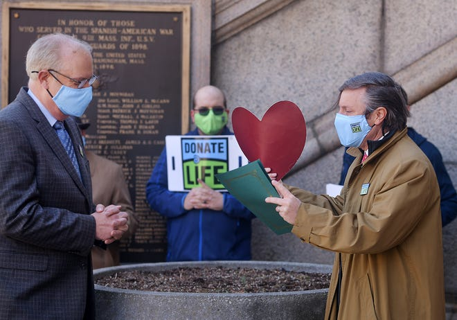 Matt Boger, right, of New England Donor Services, receives a testimonial from Worcester Mayor Joe Petty as he holds a red heart reminding people to sign up for the state's organ donor program Monday outside City Hall. April is National Donate Life Month.