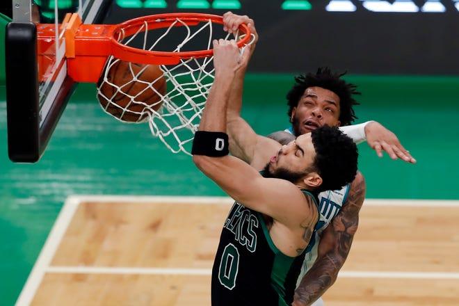 Boston Celtics' Jayson Tatum (0) dunks against Charlotte Hornets' Miles Bridges during the first half of Sunday's game.