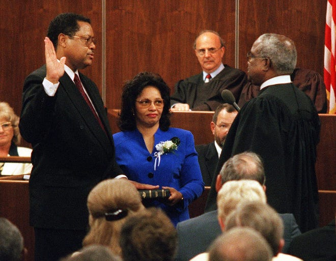 The late Judge Stephan Mickle's, left, investiture took place on Aug. 28, 1998, as U.S. District Judge for the Northern District of Florida before a courtroom full of friends, family, fellow judges and elected officials. With his wife, Evelyn, at his side, Mickle took the oath of office from Chief Judge Joseph Hatchett of the U.S. Court of Appeals, Eleventh Circuit. Senior Judge Maurice Paul is visible in the background. [Gainesville Sun File Photo by John Moran/Special to The Guardian]