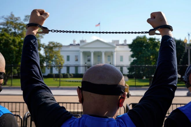 In this Oct. 1 photo, a member of the Uyghur American Association rallies in front of the White House after marching from Capitol Hill in Washington, in support of the Uyghur Forced Labor Prevention Act.