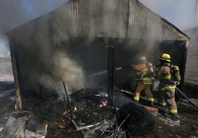 Firefighters  extinguish fire in storage building on 100 block of Fillmore Friday.