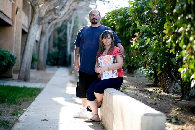 Stacy Lira and her husband of 28 years, Armando, outside their home in Victorville on March 29, 2021. She is holding a folder full of unemployment paperwork.