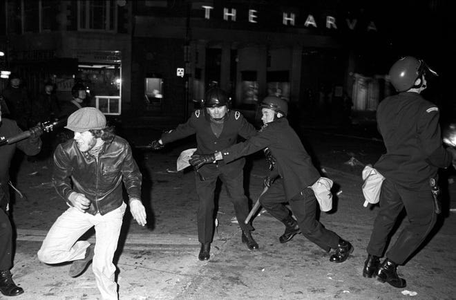 With batons in hand, police chase an antiwar protester April 16, 1970, in Harvard Square.