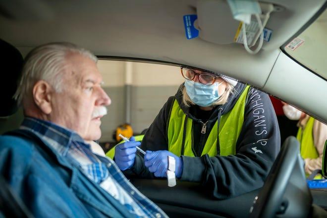 Perawat terdaftar Carrie Cooper memberikan dosis vaksin Pfizer-BioNTech kepada Bill Cavers, dari Farmington, di lokasi vaksinasi COVID-19 drive-through di dalam stasiun pemadam kebakaran nomor satu di West Bloomfield pada 5 April 2021.