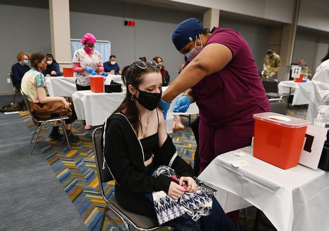 Brianne Campbell, 21, of South Lyon receives her vaccine shot from medical assistant Tiarra Brown at the walk-in clinic at the TFC Center in downtown Detroit on Monday.