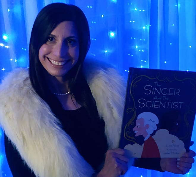 Author Lisa Rose displays her latest children's book, The Scientist and the Singer.