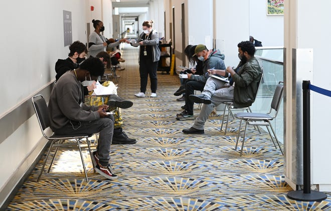 People fill out their application to receive a vaccine shot at the walk-in clinic at the TFC Center in Detroit, Monday.