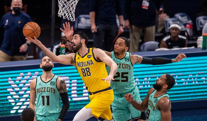 Indiana Pacers center Goga Bitadze (88) scores with a reverse layup while Charlotte Hornets forward P.J. Washington (25) defends during the first half of an NBA basketball game in Indianapolis, Friday, April 2, 2021. (AP Photo/Doug McSchooler)