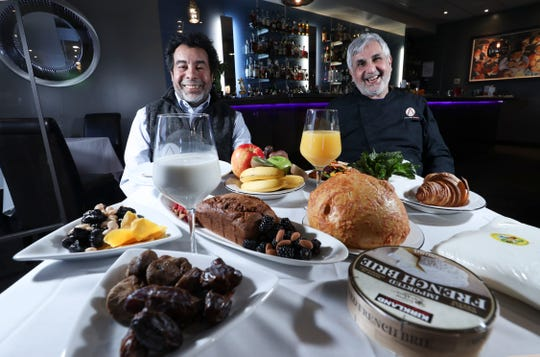 Chef Jeff Jarfi, left, of Jarfi's Catering, and Anoosh Shariat, of Anoosh Bistro, sat next to a table of items that are ideal to be consumed during periods of Ramadan when consumption is permitted in Louisville, Ky. on Apr. 1, 2021.