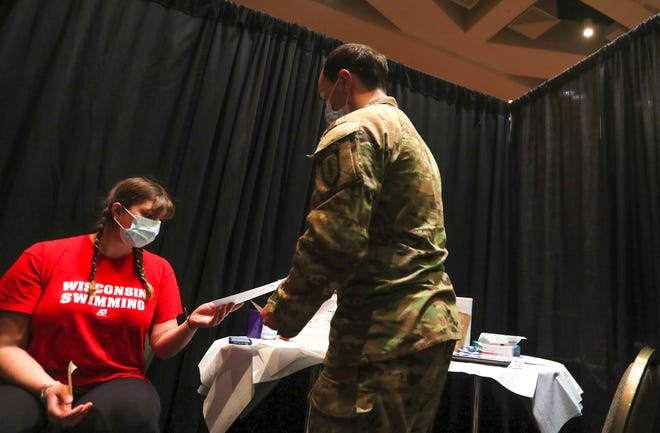 Tilly Bieganek, 17, receives information before getting her first Pfizer vaccination on Monday, April 5, 2021, at the Wisconsin Center in Milwaukee.