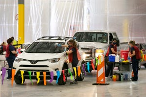 Individuals receive the COVID-19 vaccine in their vehicles on the first day of the AZDHS COVID-19 vaccine distribution site at the Dexcom regional distribution center in Mesa on April 5, 2021.
