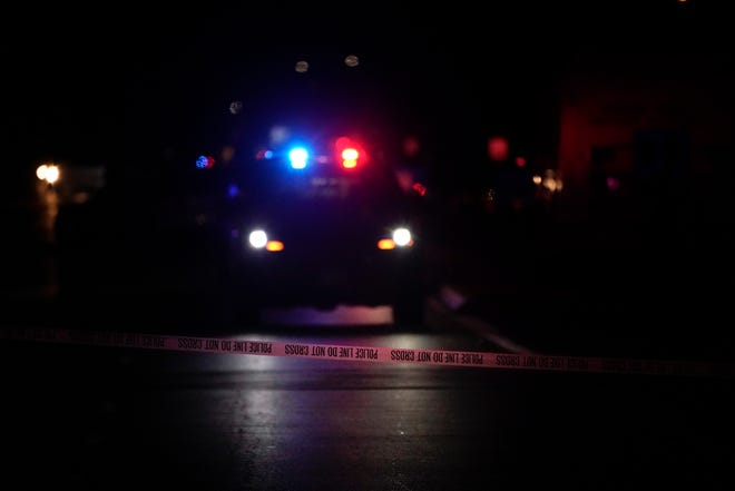 A police vehicle with flashing lights is seen behind police tape following a March 31 shooting at an office building in Orange, California.
