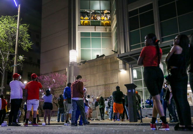 Onlookers watch from the street as inmates chant and throw things from broken windows at the St. Louis Justice Center, known as the city jail, on Sunday, April 4, 2021.