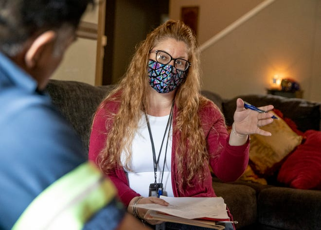 Child Protective Services investigator Arlene Castro talks to a man who initiated a case at his home in San Marcos on April 6.
