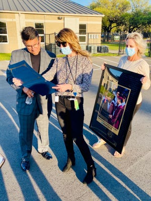 Former Round Rock school district Superintendent Steve Flores, left, is celebrated at an outdoor reception marking his retirement on March 31. Presenting him with a photo and other momentos are Jenny LaCoste-Caputo, the district's chief of communications, and Rachael Sefton, its community partnerships supervisor.