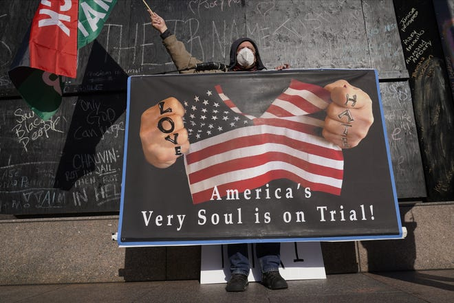 A protester holds a sign across the street from the Hennepin County Government Center Tuesday in Minneapolis where testimony continues in the trial of former Minneapolis police officer Derek Chauvin, who is charged with murder in the death of George Floyd. [AP PHOTO/JIM MONE]