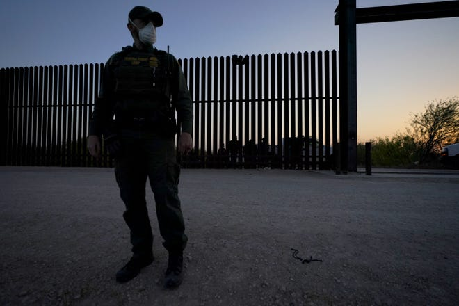 A U.S. Customs and Border Protection agent looks on near a gate on the U.S.-Mexico border wall as agents take migrants into custody, Sunday, March 21 in Abram-Perezville, Texas. [AP PHOTO/JULIO CORTEZ]