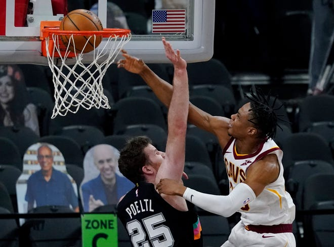 Cleveland Cavaliers forward Isaac Okoro (35) scores over San Antonio Spurs center Jakob Poeltl (25) during the first half of an NBA basketball game in San Antonio, Monday, April 5, 2021. (AP Photo/Eric Gay)