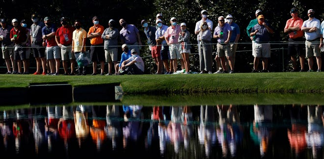 Masters Tournament patrons watch golfers skip balls across the pond at No. 16 during a practice round April 6 at Augusta National Golf Club. For the Augusta area, Masters Week always coincides with spring break.