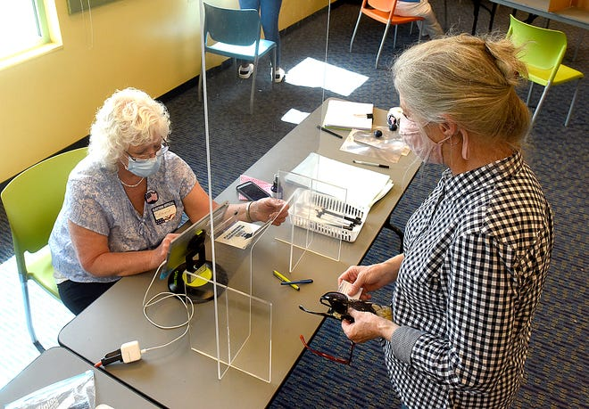 Election judge Bonnie Bedford, left, checks the voter identification and address of voter Beverly Hooker at the Daniel Boone Regional Library on Tuesday. Hooker said she wasn't concerned about voting in-person because the precinct observed social distancing and mandates masks.