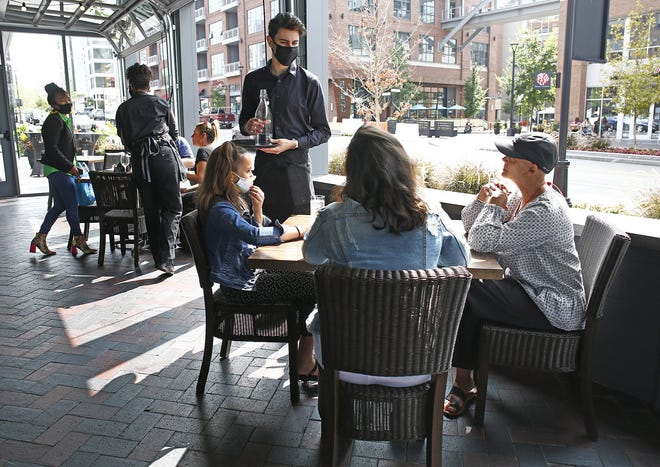 Server Andy Colondres, standing, talks with lunch diners, from left: Lili Kravchenko, her sister, Sasha Tsikhanovich, and their mom, Natalia Laschenova, at Hen Quarter in Dublin.