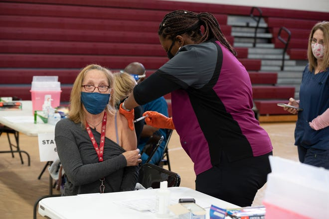 A Lake County school employee gets her COVID-19 vaccine at Tavares High School. [Cindy Peterson/Correspondent]