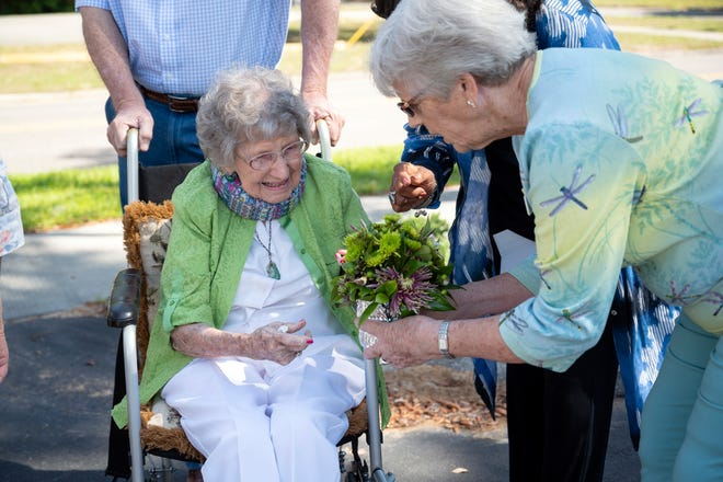 A plant is presented to Ruth Squire at the tree dedication ceremony at the Eustis Memorial Library on Tuesday. [Cindy Peterson/Correspondent]