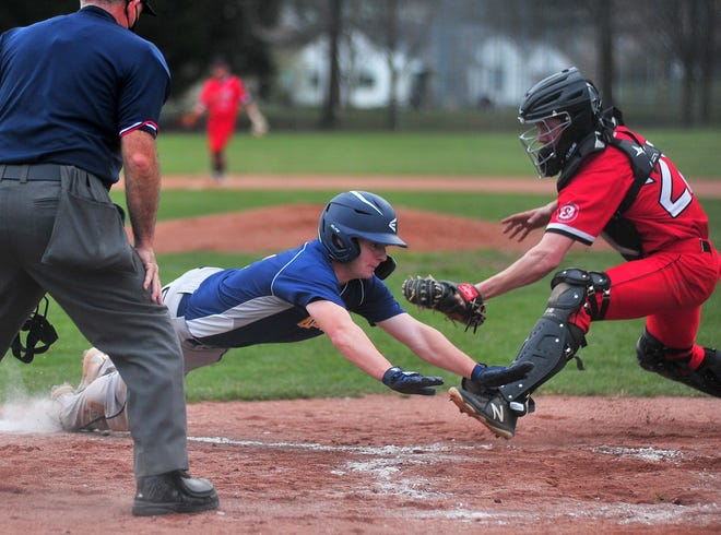 Hillsdale's Daniel Painter slides under Orrville catcher Eion Ogg to score for the Falcons.
