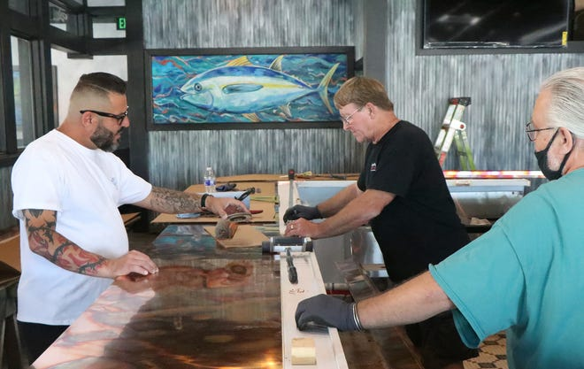 Stephan Stavris, left, is a co-owner at Big Tuna Bar and Grill. He talks with contractors building the bar Tuesday as area restaurants continue searching for employees.