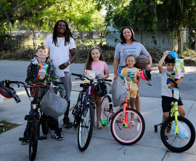 """Ormond Beach resident Charles Leon Ivy kicked off his """"Bike and a Book"""" on Monday. Six-year-old Enzo Chappell and his three siblings each received a bike and a book."""