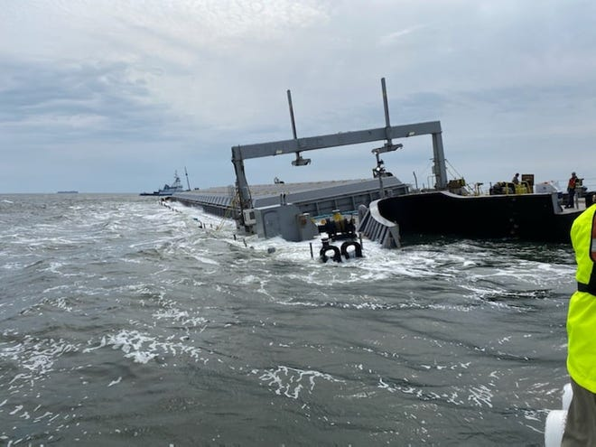 The Coast Guard takes a close look at the stranded barge Bridgeport after it grounded about a mile off Jacksonville.