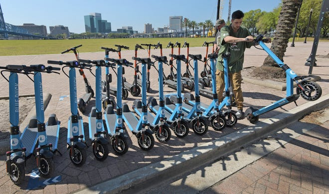 Jake Ross delivers freshly charged Blue Duck scooters to a scooter parking zone near the site of the former Jacksonville this week. Blue Duck is one of several scooter rental companies now operating downtown, each with different payment models and apps to use their products.