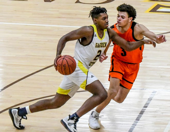 Garden City Community College's Denver Jones, left, drives past Neosho County's Cougar Downing on his way to scoring a basket during a February game at Perrryman Athletic Complex.