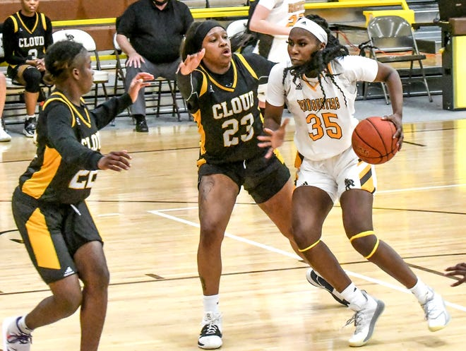 Garden City Community College's Justis Odom, right, drives the lane between Cloud County's LeYanna McGinnis (23) and Idalis Lee for a basket Monday at Perryman Athletic Complex.