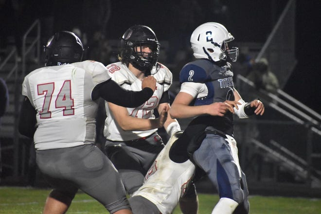 Orion's Josh Fair brings down the Monmouth-Roseville quarterback late in the game on Thursday, April 1, in Monmouth. Also closing in on the quarterback are Zack Riddell (74) and Jayson Johnson (72).