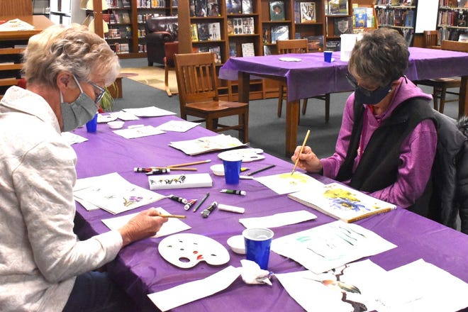 Practicing their Chinese brush painting skills are Nancy West, and Pat Larson, who were busy on Thursday, April 1, at Western District Library, Orion.