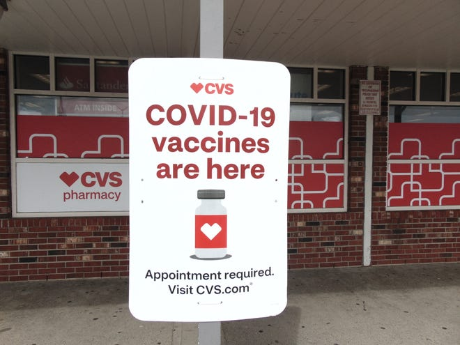 A sign in front of CVS related to COVID-19 vaccines.