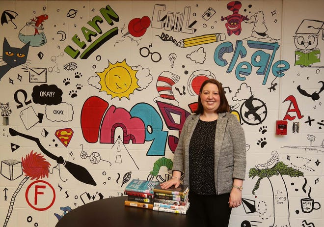 Angela Wojtecki, the Nordonia Hills District library media specialist/technology integrationist, stands inside the library at Nordonia High School with a few of the new nonfiction books she added to the library's content. She is pictured in front of a mural painted by students.