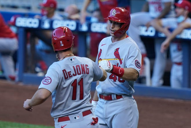 St. Louis Cardinals' Paul DeJong (11) and Paul Goldschmidt (46) celebrate after scoring in the first inning of a baseball game against the Miami Marlins, Monday, April 5, 2021, in Miami.