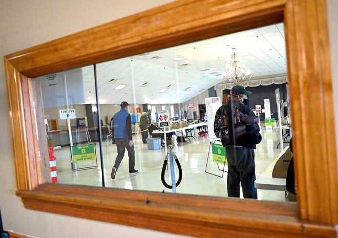 The voting scene is reflected in the bar's one-way mirror at the Milford Portuguese Club, where four Milford precincts cast their ballots in the town election, April 6, 2021.