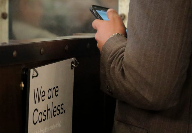 """A restaurant sign alerts customers that it's now """"cashless."""" One year ago, the coronavirus pandemic forced business closures and lockdown orders. In the 12 months that followed, many aspects of daily life have changed, including how we handle money, both physically and philosophically. [AP File Photo/Bebeto Matthews]"""