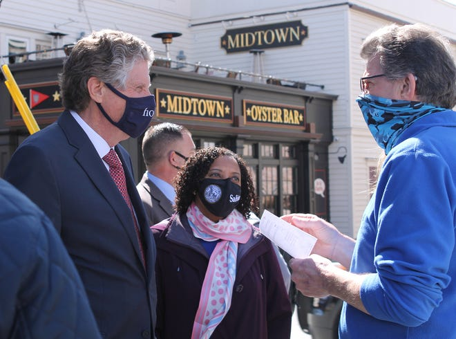 Red Parrot owner Russel Dulac, right, talks with Gov. Dan McKee on Tuesday during a small business stroll through the city. Looking on its Lt. Gov. nominee Sabina Matos.