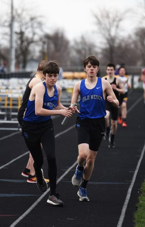 Colo-NESCO's Alex Rouse takes the baton from his twin brother Ben during the Class B 4 X 800-meter relay at the Cub Relays March 30 in Nevada.