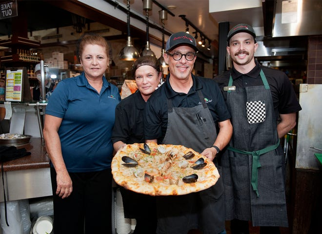 Maria Vidal, from left, Ivon Rodriguez and Maurizio and Joseph Ciminella hold pizza topped with seafood at Amici Market in Palm Beach recently.