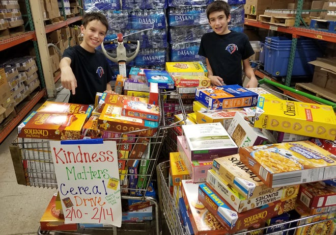 Jett and Luke Justin pose with some of the boxes of cereal they collected during a Cereal4all drive at Del Prado Elementary School in Boca Raton.