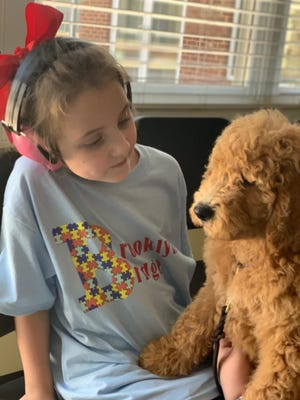 Eight-year-old Brooklyn Bradshaw with her Goldendoodle puppy Bridge being trained by Pride and Prejudoodles in Lynchburg on July 18, 2020 to be a certified emotional support service dog.