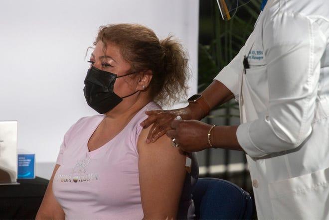 Maria Josefa Mendoza Alvarado, left, receives a COVID-19 vaccination during a recent press event at the Stockton Arena in downtown Stockton. CLIFFORD OTO/THE STOCKTON RECORD