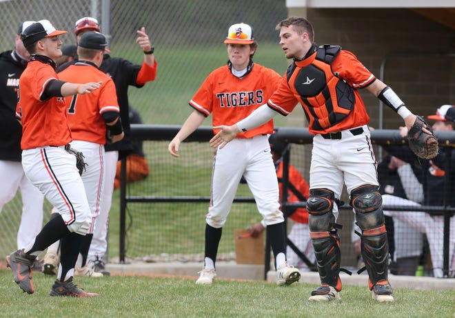 Massillon catcher Luke Sabo, right, greets teammates after an inning during the Tigers' win over GlenOak on Monday.