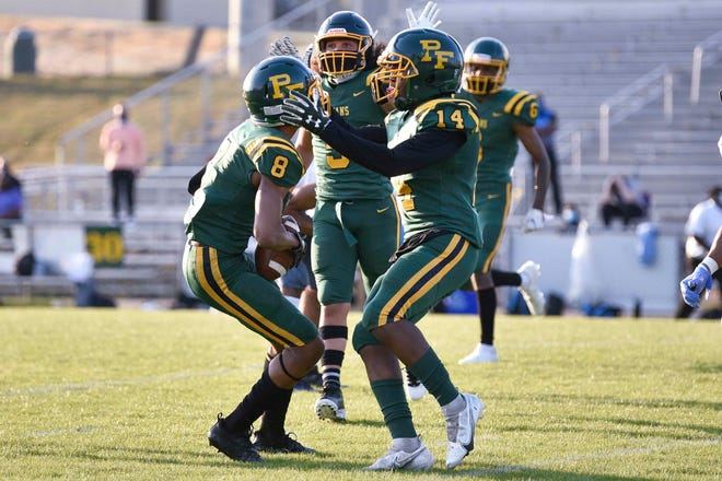 Pine Forest's Justin Eaglin (8) celebrates with Gregory Washington (14) after an interception. The Trojans' defense put together another stellar effort in a 21-13 win against Overhills.