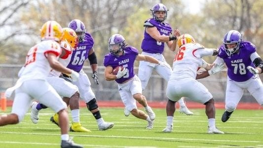 Southwestern Assemblies of God University quarterback Jordan Barlow fakes a throw as running back Keaton Dudik (5) carries the football on a draw play during Saturday's game against Ottawa University in Surprise, Ariz. The Lions lost to Ottawa, 37-7.